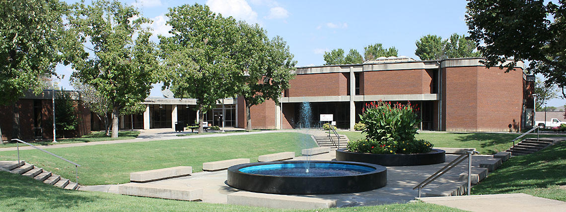 Wide View of Campus Courtyard With Full Foliage and Fountain Running