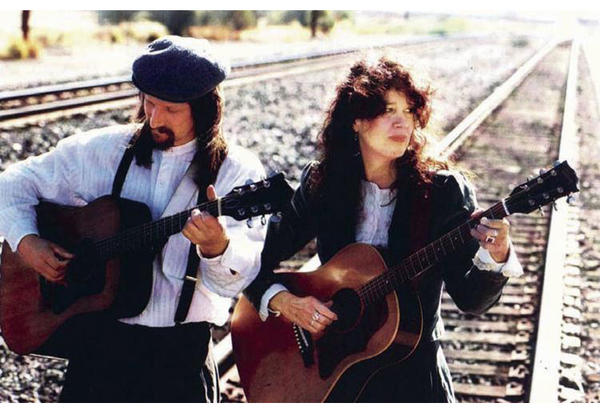 Phil Lancaster and Alison Moore profile picture, both playing guitars while standing on railroad tracks, but don't worry, there doesn't appear to be a train passing anytime soon.