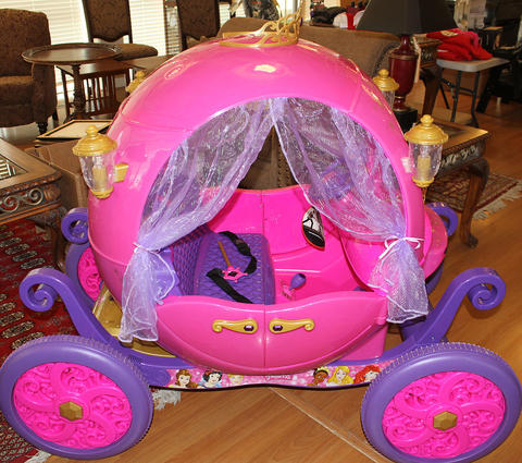 Side view photo of a pink motorized carriage with purple wheels.