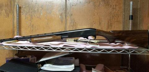 Side view photo of  a Remington 20-gauge shot gun with a gold trigger.