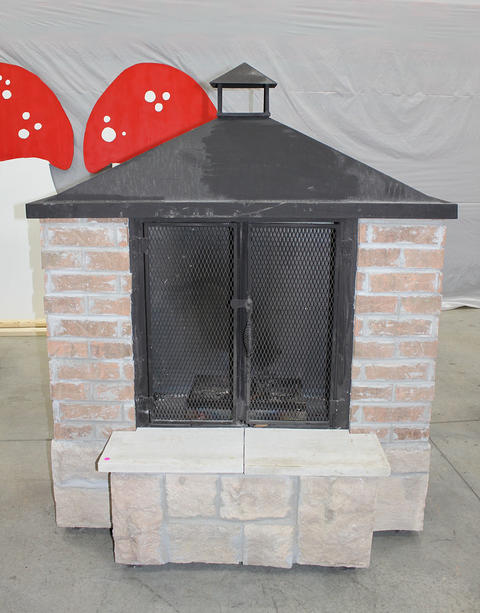 Brick and stone outdoor fireplace with glass doors.