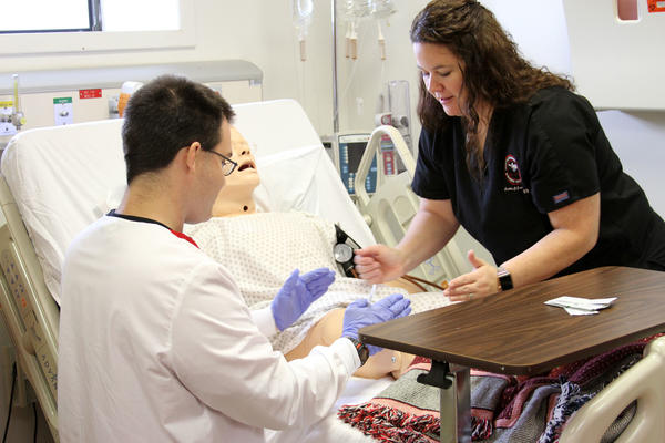 Nursing Student and Instructor Checking Vitals on a Training Dummy