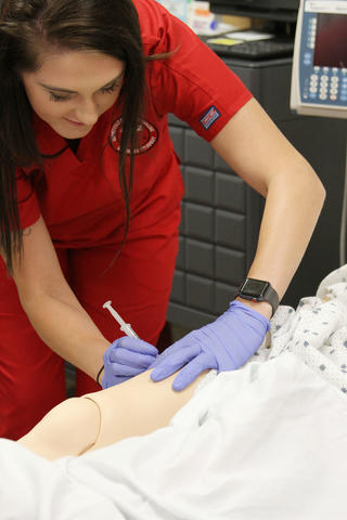 Nursing Student Learning How to Insert Needle Into Arm