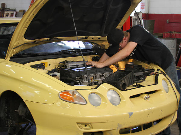 Student Working Under Hood of a Yellow Hyundai