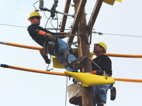 Two Linemen Working at Top of Utility Pole