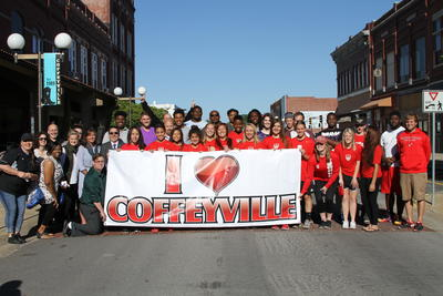 "Group of Local Citizens Holding Up a Large ""I Love Coffeyville"" Banner"