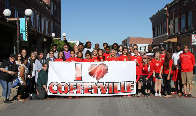 Local Group Holding I Love Coffeyville Banner in Downtown