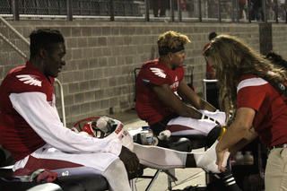 Athletic Trainer Taping Ankle of a Red Raven football player
