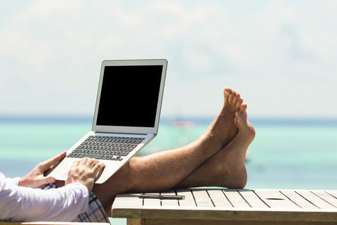 Man Using Laptop on Beach Stock Photo