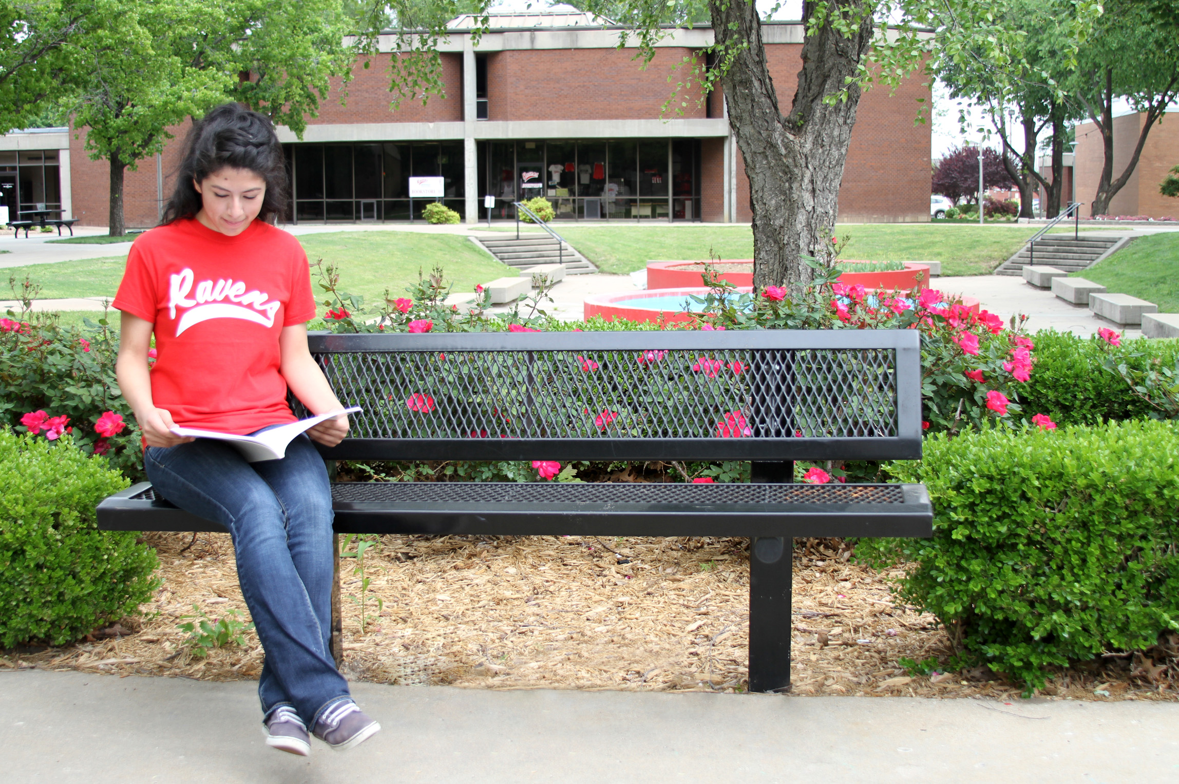 Student Sitting on Bench in College Courtyard