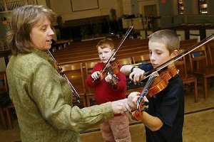 Students practicing violin with instructor