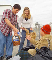Two students providing goods to a homeless man