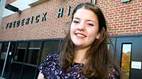 Student Success Stories (student in front of FCPS building)