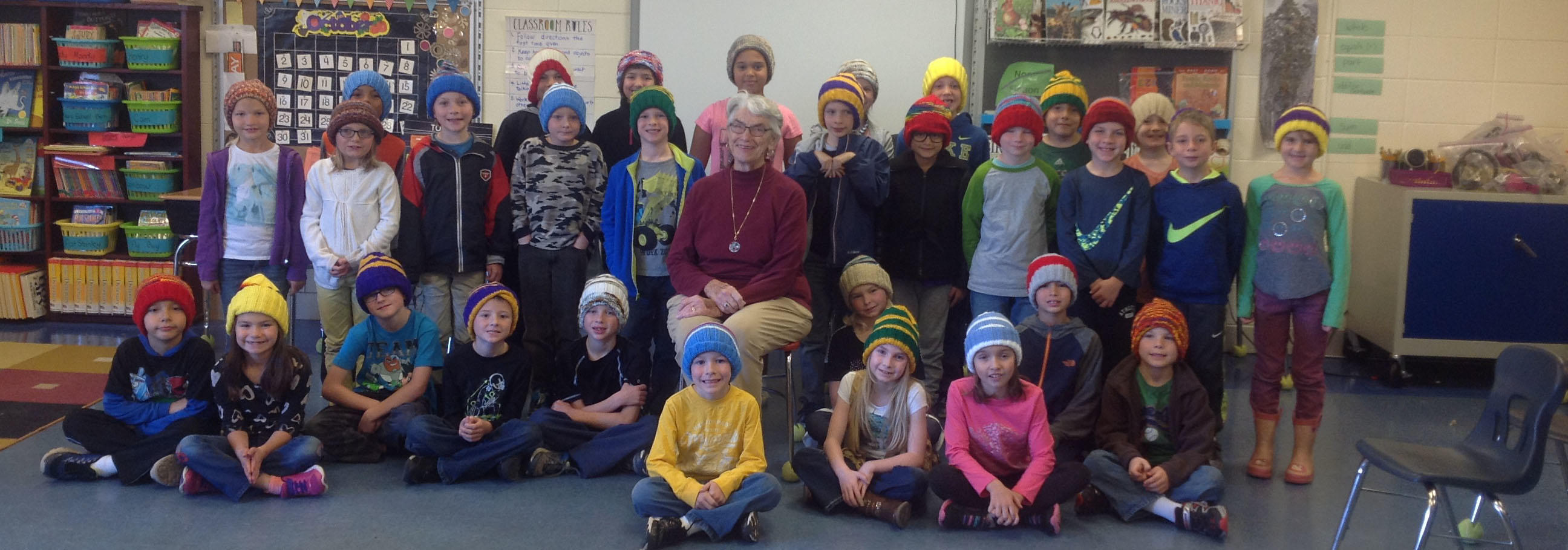 The second graders at South Terrace, pictured with knitter Char Mattson, are wearing new hats.