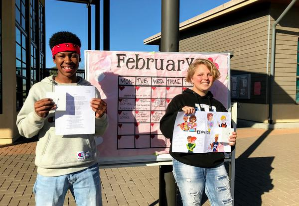 two students stand side by side, holding a poem and a drawing, as well as AirPods