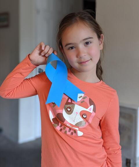 Image of a student holding up a paper blue ribbon