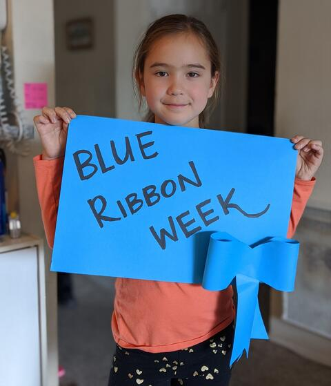 "Image of a student holding up a blue sign that reads ""Blue Ribbon Week"""