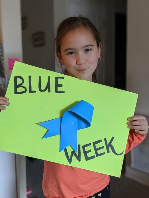 Image of a student holding up a green poster that says Blue Ribbon Week