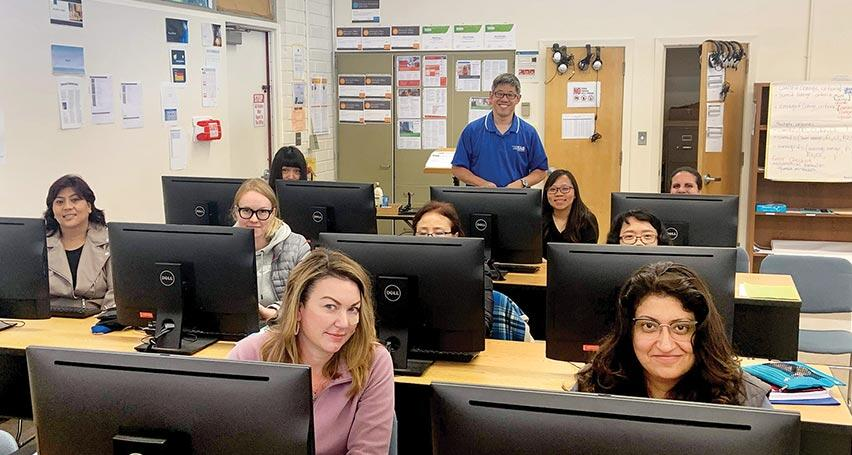 teacher with students in computer classroom