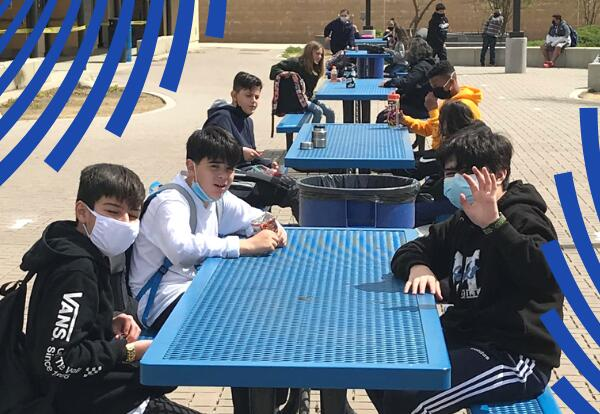 A group of students sit on a blue lunch bench, each wearing a mask. One student is waving.