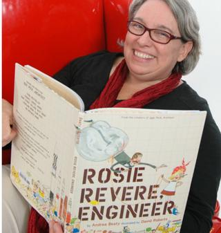Photo of author Andrea Beaty holding a copy of her book Rosie Revere, Engineer; ANDIE PETKUS PHOTOGRAPHY