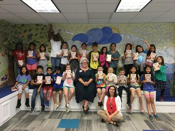 Photo of Andrea Beaty and students from Highland School holding their signed copies of Rosie Revere and the Raucous Riveters