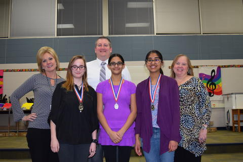 Adults pose with female students with medals around their necks