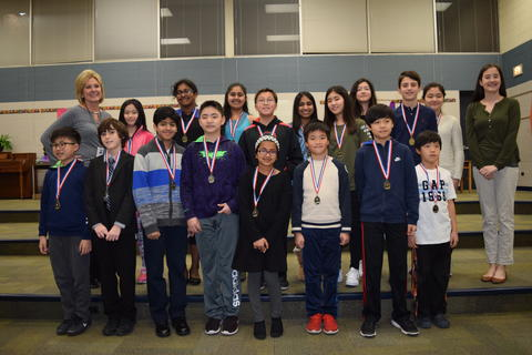 Larger group of adults and students posing with medals