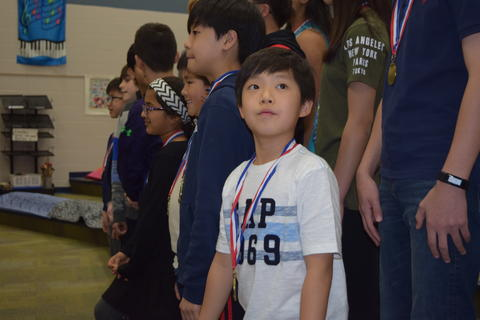 Male student with medal looks away from and above camera