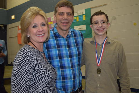 Proud parents pose with male student wearing medal