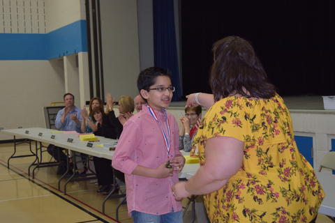 Adult points male student with medal toward table