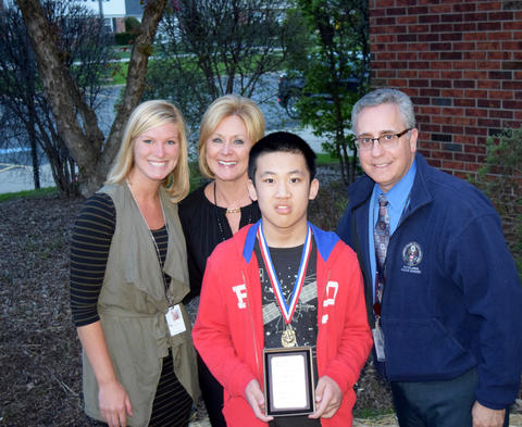 Adults pose with male student who was the Highest SAT math scorer
