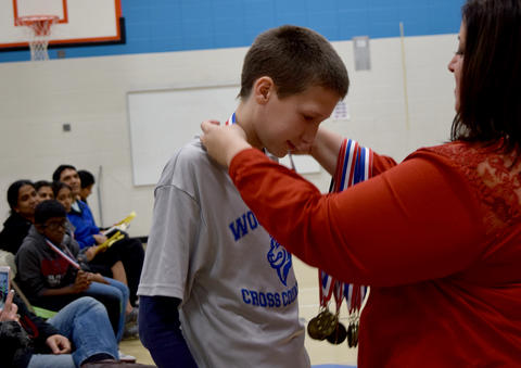 Male student bows head to receive medal
