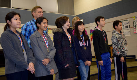 Side shot of students posing with medals