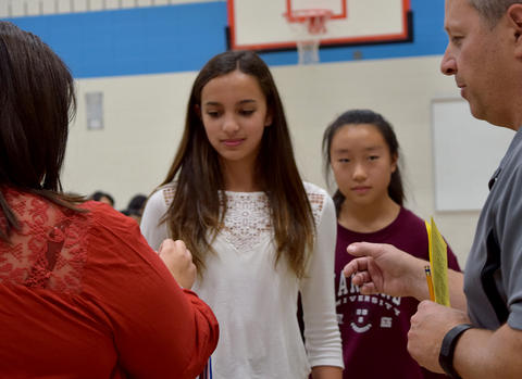 Two female students stand in line to receive medals