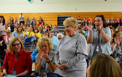 Mrs. Hannon stands and is applauded by the crowd