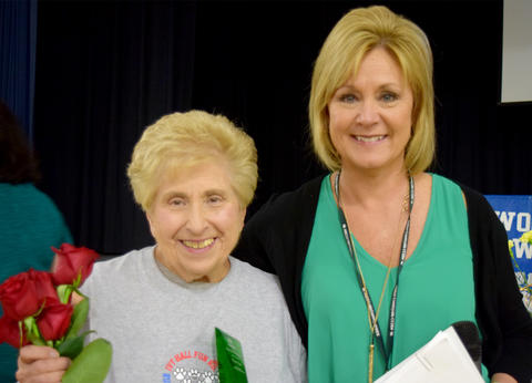 Mrs. Hannon poses with roses and Superintendent Schmidt