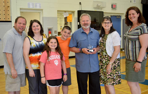 Joe Star poses with family, colleagues, and a crystal apple silver thread award