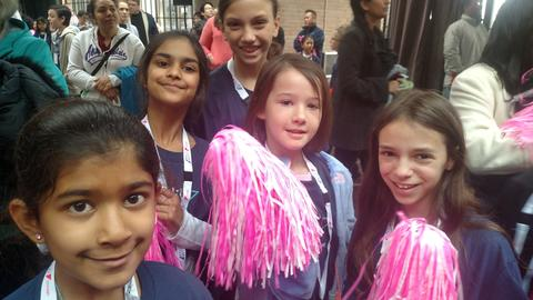 Several participants; two are holding pink and white pom poms