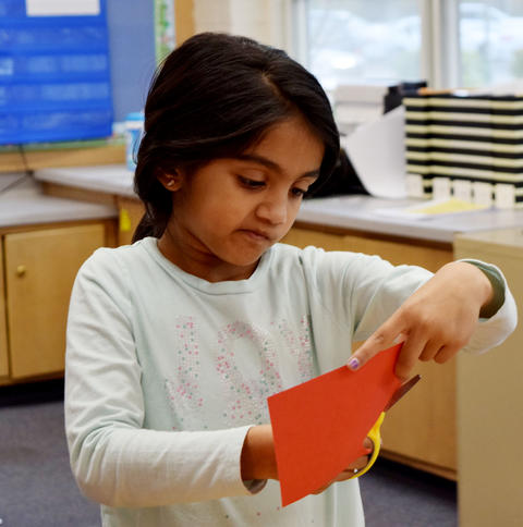 Female student cuts handprint out of red construction paper