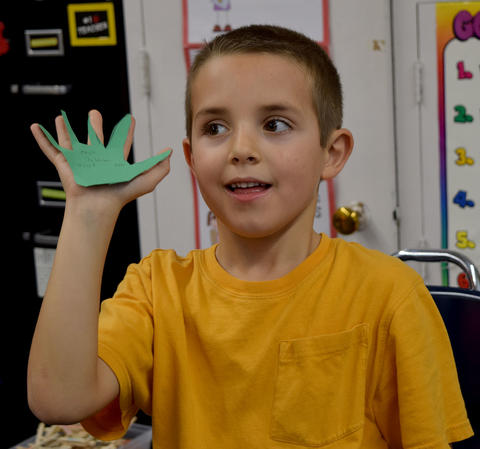 Male student holding a green construction paper hand in his hand