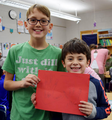 Two male students smile and hold red piece of paper