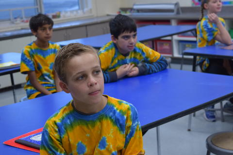 Students in blue and yellow tie dye shirts listening
