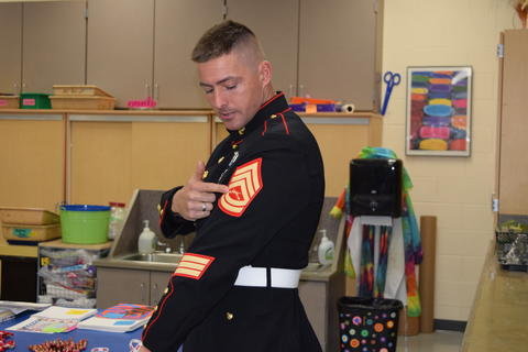 Marine pointing to insignia on his arm, explaining meaning