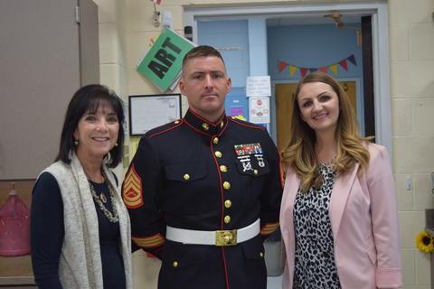Teachers pose with Marine