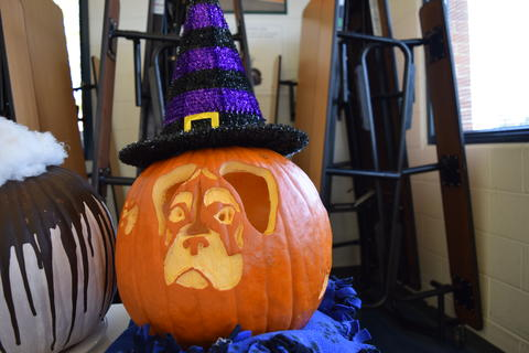 Pumpkin carved to look like a dog, with a purple witches hat on top