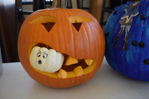 Carved pumpkin has little white pumpkin sticking out of its mouth