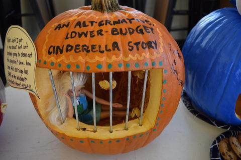 Pumpkin carved with bars on mouth and a Barbie doll inside