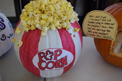 Pumpkin decorated to look like popcorn container, with popcorn at top
