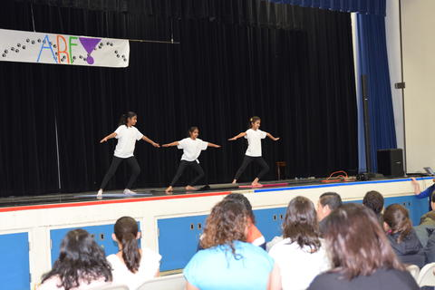 three girls performing yoga stretches onstage
